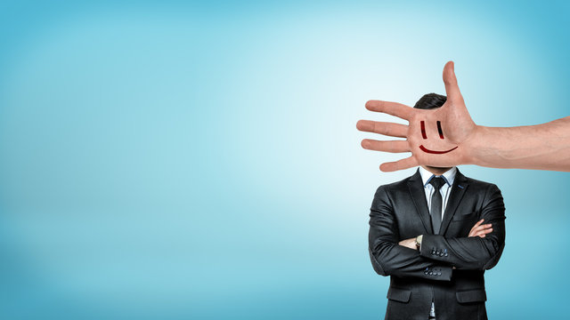 A businessman stands in a front view with folded arms behind a giant male hand with a smiley face covering his head.