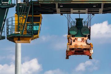 Orang gelber Lastenkran schwebt über Transportgut, Frontansicht, closeup