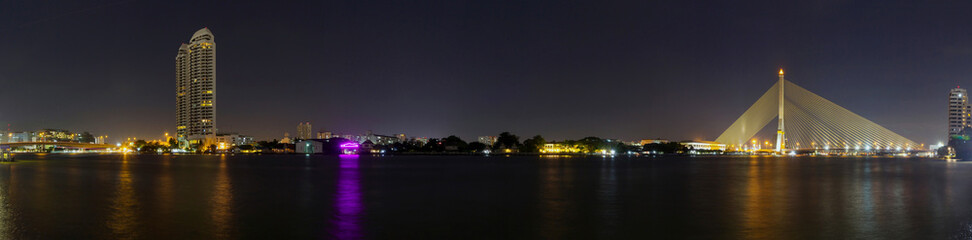 Panorama of High building and Big Suspension bridge with lighting in night time / Rama 8 bridge in night timev