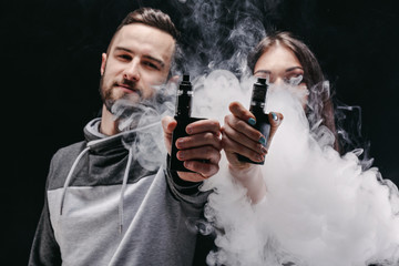 Couple vaping e-cigarette with smoke on black