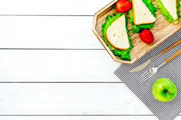 Sandwiches with lettuce and tomatoes for picnic on tablecloth on white wooden background top view copyspace