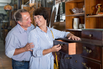 Man with wife are choosing old buffete in antique shop