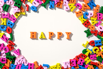 The word Happy is lined with colourful wooden letters on a white table with scattered in a circle with letters
