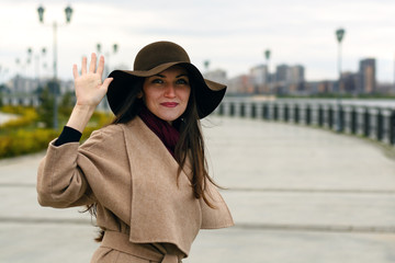 Happy stylish girl in a coat with belt and big hat greeting showing hand gesture. The concept of welcome, hello, walking with friends