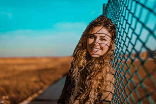 Portrait of urban young woman leaning on wire fence.