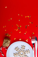 On a red background with a place for an inscription in a plate with wooden snowflake, next to a knife and fork.