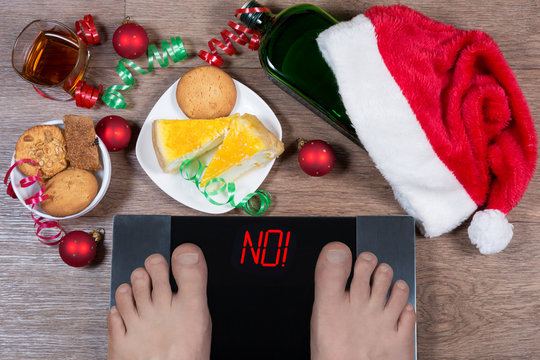 "Digital scales with male feet on them and sign ""no!"" surrounded by Christmas decorations, sweets and bottle of alcohol. Shows how unhealthy lifestile during xmas holidays effects our body."