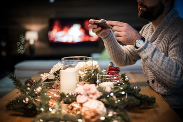 Bearded man photographing decorated christmas table