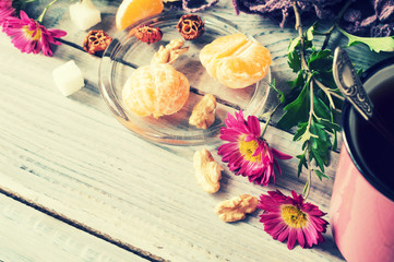 Cup of tea, flowers and tangerine on a white wooden table
