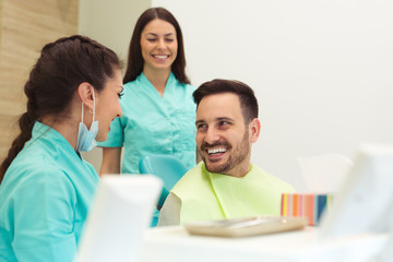 Portrait of a female dentist and young man in a dentist office