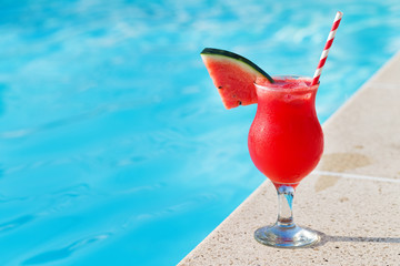 Glass of fresh watermelon smoothie juice drink on border of a swimming pool