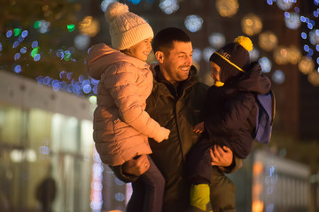 Father is holding his children. They are talking and smiling. It is an outdoors evening photography. There is blurred bokeh lights on background. Theirs emotions are really candid.