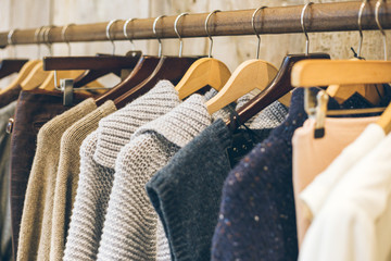 Conscious / ethical fashion trend concept.  Warm winter ladies clothes collection with old school hand knitted jumpers and cardigans on wooden hangers.