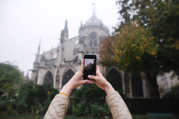 Women hands with phone, tourist taking a picture of the Notre dame de Paris