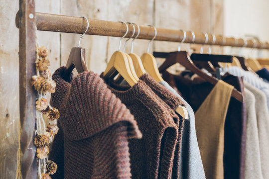 Conscious / ethical  fashion trend concept.  Warm winter ladies clothes collection with knitted jumpers, dresses and cardigans on wooden hangers.