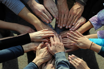 lots of hands come together in a circle