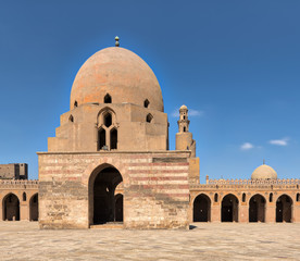 Courtyard of Ibn Tulun Mosque, Cairo, Egypt with ablution fountain and minaret in far distance