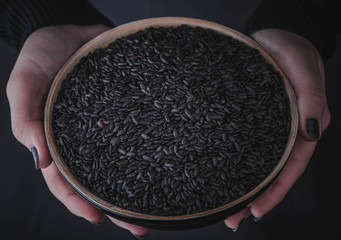 Woman is holding a bowl with black wild rice.