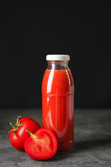 Bottle of tomato juice on table against black background