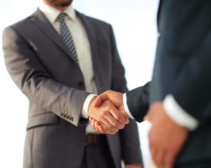 Friendly smiling businessmen handshaking. Business concept photo