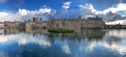 Panorama of the Dutch parliament building reflection on the pond under a freezing bright midday