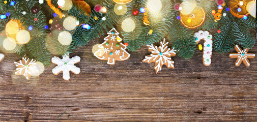 christmas gingerbread iced cookies with fir tree flat lay border, copy space on wooden background banner