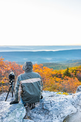 Sitting young man photographer with camera, gear, and tripod on cold autumn morning in jacket in Bear Rocks, West Virginia taking pictures of sunrise