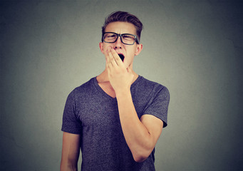Young man yawning with hand over his mouth