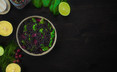 Black wild rice with lemons, limes and berries on the dark wood table. Top view