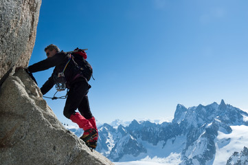 Climbing in Chamonix. Climber on the stone wall of Aiguille du Midi