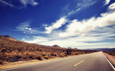 Vintage stylized picture of a Death Valley deserted road, travel concept, USA.