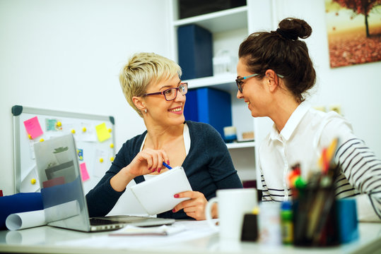 Two beautiful middle aged women colleague working together and looking each other while sitting at the desk in the office.