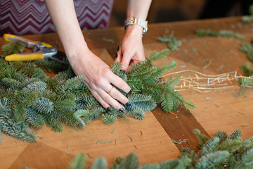Florist at work: woman hands making christmas decorations garland of fir. Happy new year dinner feast