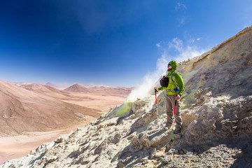 Fototapete - Tourist adventurer backpacker standing smoking volcano mountain peak, Bolivia.