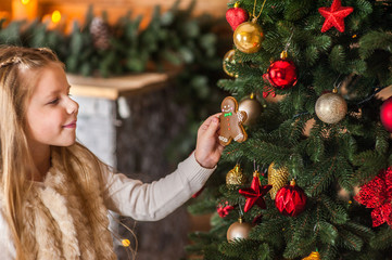 Girl holding, playing, eating a gingerbread Christmas man on a background of Christmas tree and Christmas lights
