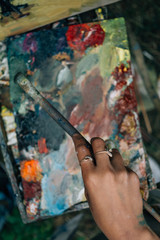 Artist hand paintbrush and palette, top view, toned