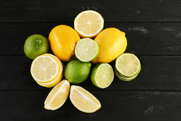 Ripe limes and lemons on black wooden table