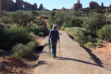 Woman carrying a tripod and a walking stick down a trail at Double Arches