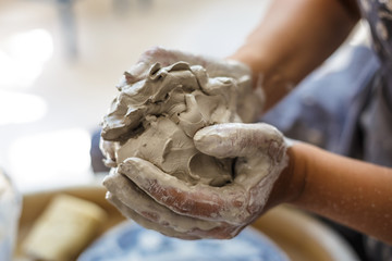 Female potter hands knead wet white clay Fototapete