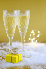 New Year's composition: Two glasses with champagne on a gold background.