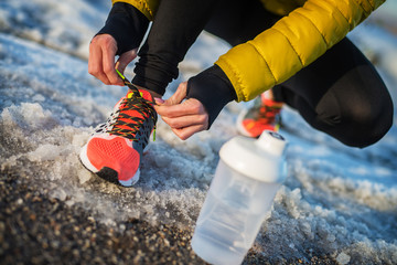Close up of woman's hands tying shoelaces on snowy winter road with a bottle of water in front.