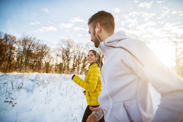 Active athletes sportive couple jogging with strong persistence on the snow covered road in nature in the morning.
