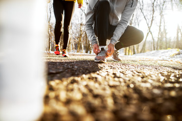 Close up of sport active man in sportswear kneeling on the road and tying shoelaces in the sunny winter morning outside in nature with a girl next to him.