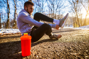 Close up of sporty active man in sportswear with earphones sitting on the road and puts shoes on in the sunny winter morning outside in nature.