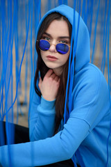 young beautiful woman fashionably posing in blue sunglasses on the blue background from ribbons. Overcast