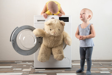 Parents bought a new washing machine. The children try to turn it on and wash the soft toys. Happy boys are playing at home.