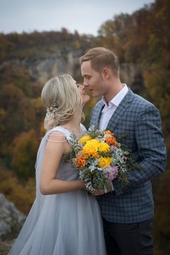 Beautiful couple in the mountains of the wedding in autumn the bride and groom with a bouquet of yellow flowers