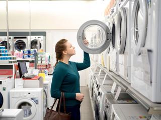 Beautiful woman buying washing machine in supermarket.