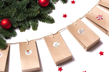 Handmade tinkered advent calendar with paper bags and stickers hanging from fir branches and red stars on white background
