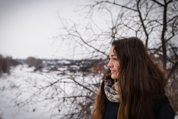Pensive and romantic girl with beautiful long hair on the winter background looking away on the winter landscape